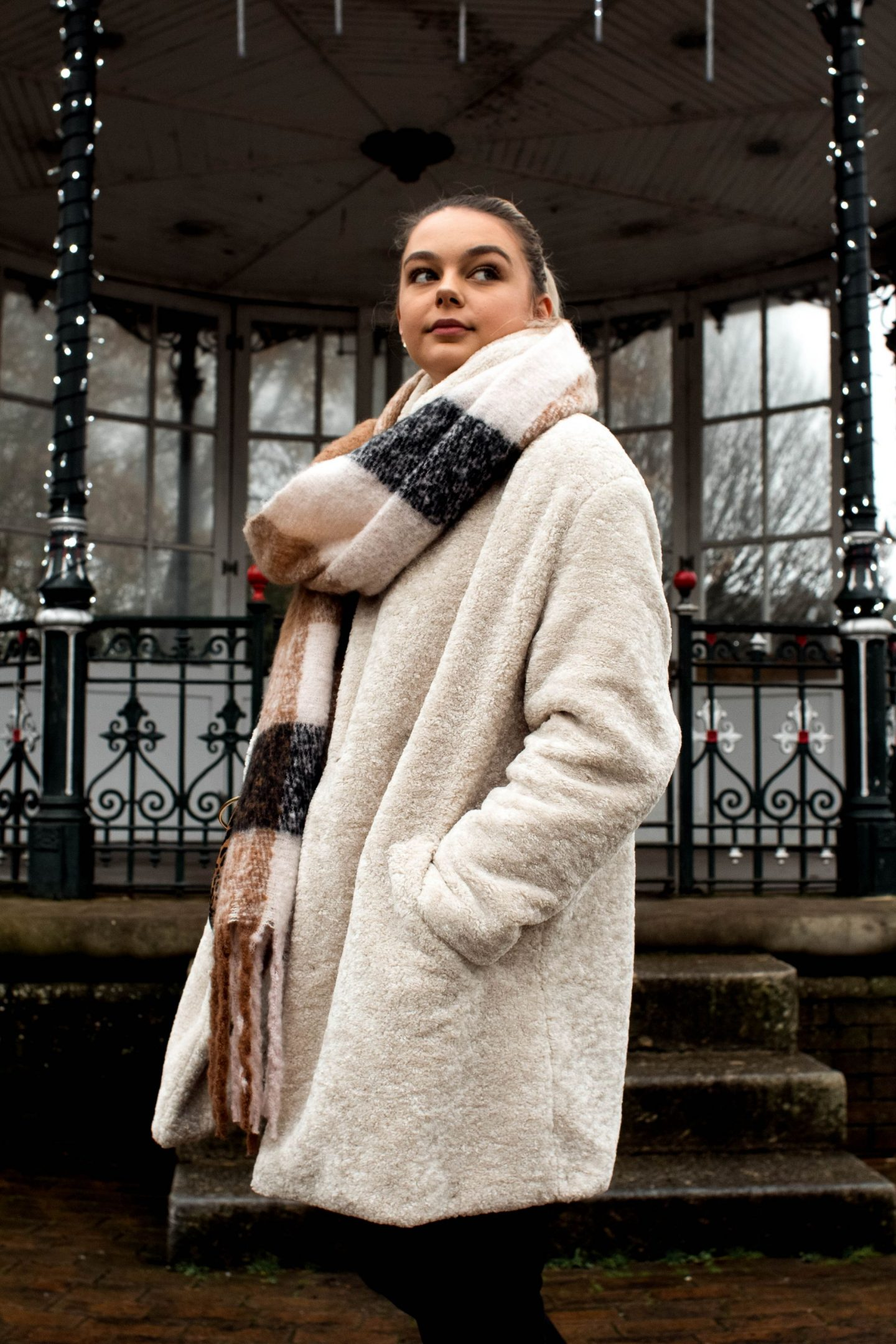 This image is a photo of me in my new white and fluffy coat, an oversized scarf and black jeans. I am stood in front of an old band stand in Dartmouth that has while fairy lights wrapped around it. Very festive for this blog post about my new chapter.